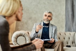 Professional psychoanalyst listening to young caucasian woman talking about her problems during appointment in office, selective focus. Psychotherapy concept