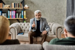 Professional psychoanalyst talking to upset couple of spouses sitting on sofa during session in cabinet, selective focus. Psychotherapy concept