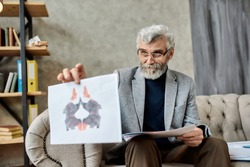 Professional psychotherapist showing inkblot test pictures to patient during session in office, selective focus. Psychotherapy concept