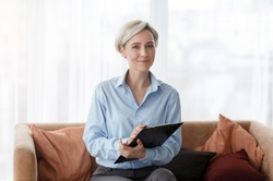 Professional Psychotherapy. Successful Psychologist Holding Folder Smiling To Camera Sitting On Sofa In Office.
