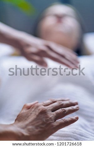 Professional Reiki healer doing Reiki treatment to young woman in health spa center. Healing and balancing heart and crown chakras.