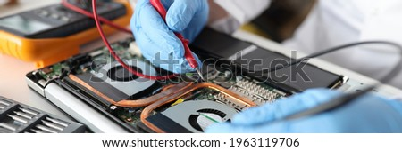 Professional repairman holding red tester in rubber gloves over laptop closeup Photo stock ©