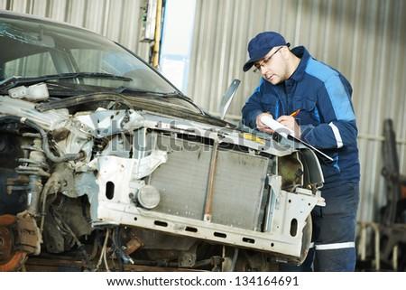 professional repairman worker in automotive industry at repair determination of damaged metal body car