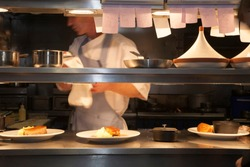 Professional restaurant kitchen with food being prepared and set on kitchen pass for waiting staff.