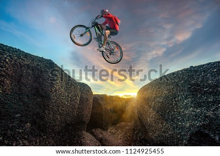 Professional rider is jumping on the bicycle, with background of sunset, racing in high speed competition