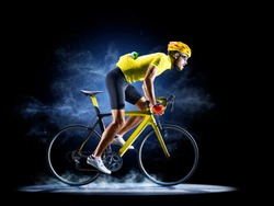 Professional road bicycle racer in action isoated on the black background