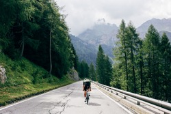 Professional road cyclist on fast and light carbon bicycle descends mountain road in Alps Dolomites. Fit and athletic man on recreational ride trip or training camp, enjoy time outdoors on bike