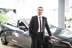 Professional salesman smiling in front of a new car