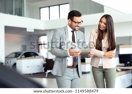 Professional salesperson selling cars at dealership to buyer #1149588479