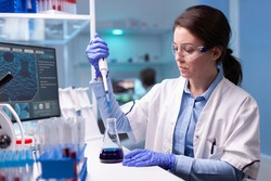 Professional scientist taking sample for medical experiment. Chemist researcher working in laboratory with micropipette to discover vaccine against coronavirus.