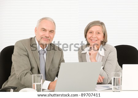 Professional senior businessman pointing at computer with woman colleague discussing
