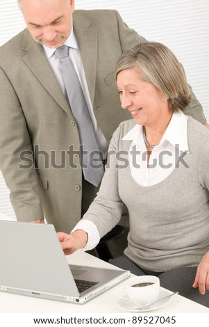 Professional senior businesswoman looking at computer with man colleague