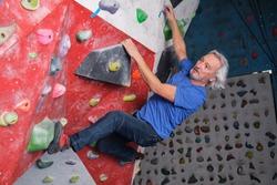 Professional senior man climbing on an artificial rock climbing wall. Extreme sports concept.