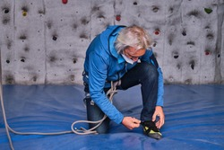 Professional senior man wearing protective face mask tying his climbing shoes getting ready to climb on an artificial rock climbing wall. Extreme sports concept.
