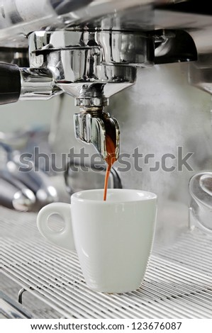 Professional silver gray coffee machine with white cup and pouring drink