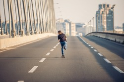 Professional skateboarder riding a skate over a city road bridge, through urban traffic. Free ride skateboards