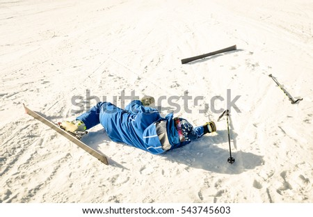 Professional skier after crash accident on skiing resort slope - Winter sport emergency concept with athlete needing help assistance on dramatic trouble situation - Warm sunny afternoon color tones #543745603