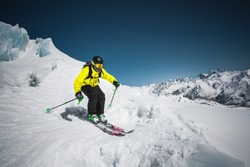 Professional skier at the speed before jumping from the glacier in winter against the blue sky and mountains