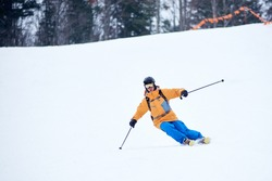 Professional skier concentrated on skiing down on steep ski slope. Proficient technical carving skiing. Net on slope edge. Wooded mountain top on background. Extreme winter activities concept