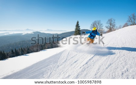 Professional skier riding the slope on a beautiful winter day ski resort recreation travelling tourism vacation extreme adrenaline #1005987898
