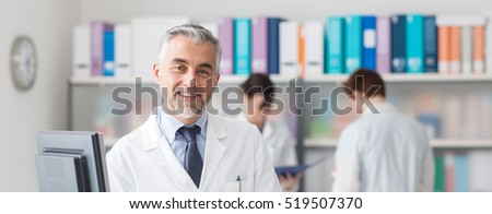 Professional smiling doctor posing at hospital, medical staff working on the background