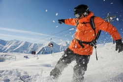 Professional snowboarder in orange sportswear riding down a mountain slope against the cable car and blue sky