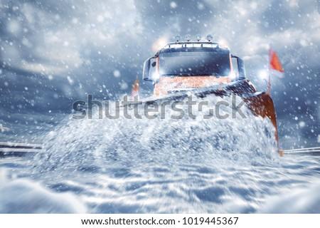 Professional snowplow on a snowy road - Shutterstock ID 1019445367