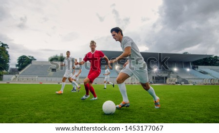 Professional Soccer Player Leads with a Ball, Masterfully Dribbling and Bypassing Sliding Tackles of His Opponents. Two Professional Football Teams Playing. Low Angle Shot. #1453177067
