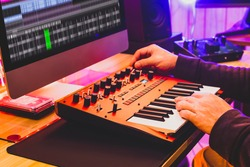 professional sound designer hands playing and tweaking analog synthesizer keyboard knobs for editing sound in post production studio. sound design concept