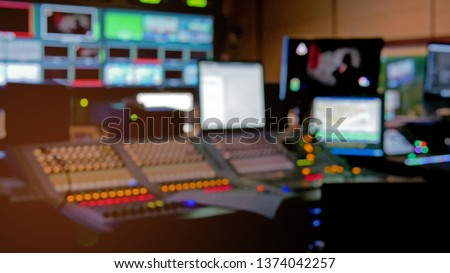 Professional sound engineer's console. Television Broadcast, working with video and audio mixer, control broadcast in recording studio. blurred background, monitors.