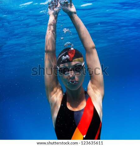 professional sport swimmer floating up underwater in blue with small air bubbles on her face