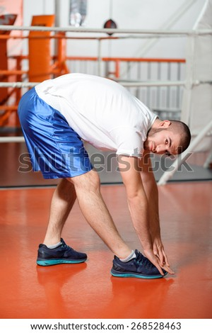 Professional sport. Young fit man stretching in a boxing ring and looks at a camera