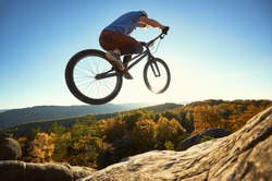 Professional sportsman cyclist jumping on trial bike on top of rock. Man making acrobatic trick on summer sunny day, blue sky, forest, sunset on background. Concept of extreme sport active lifestyle