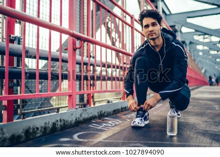 Professional sportsman dressed in active tracksuit listening music player in earphones and tied up laces on stylish sneakers during morning workout in urban setting on bridge for getting sportive goal