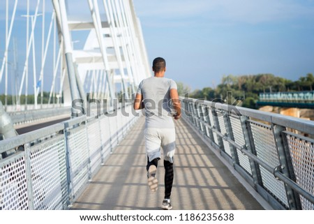 Professional sportsman running on the bridge. Athlete training and healthy lifestyle.
