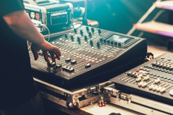 professional stage sound mixer closeup at sound engineer hand using audio mix slider working during concert performance
