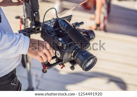 Professional steadicam operator uses a 3-axis camera stabilizer system on a commercial production set