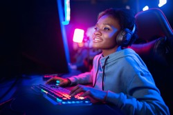 Professional Streamer African young woman cyber gamer studio room with personal computer armchair, keyboard in neon color blur background.