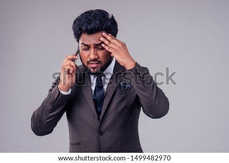 professional stress problem at work:portrait of depressed business upset indian man speaking by mobile phone about nervous deal in studio white background.