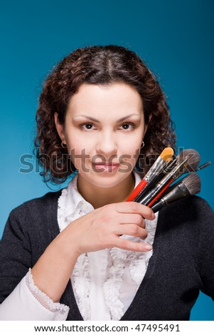 Professional stylist with make up brushes on blue background