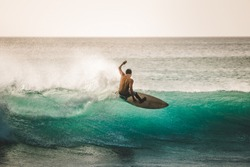 professional surfer riding waves in Bali, Indonesia. men catching waves in ocean, isolated. surfing at sunset