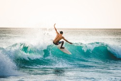 professional surfer riding waves in Dreamland Beach, Bali, Indonesia. men catching waves in ocean. Tail slide water surf, action water board sport