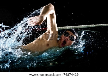 Professional swimmer crawl freestyle isolated black background