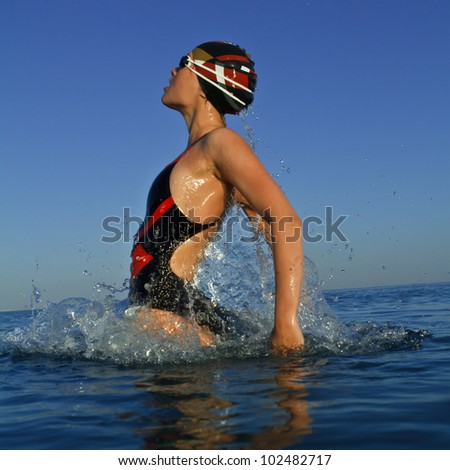 professional swimmer jumping from sea water with splashes