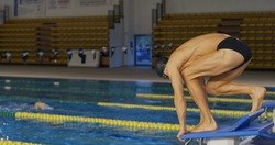 Professional swimmer with googles trains with effort and dedication to win the race by swimming in a freestyle pool. Concept of sport, swimming pool, competition, fitness.