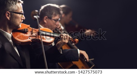 Professional symphonic orchestra performing on stage and playing a classical music concert, violinist playing in the foreground, arts and entertainment concept