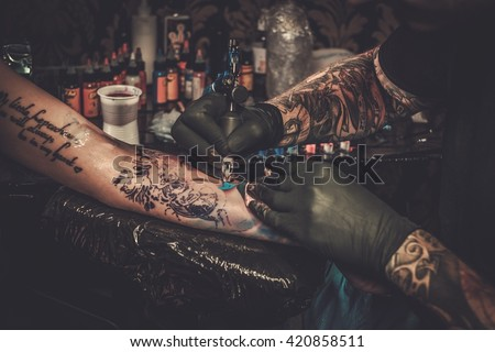 Professional tattoo artist makes a tattoo on a young girl's hand.  #420858511