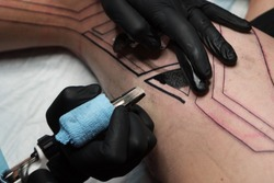 Professional tattoo artist makes tattoo on man leg. Process. Introduces black ink into skin using needle from tattoo machine. Close up of tattoo machine. Tattooing. Master creating picture on leg.