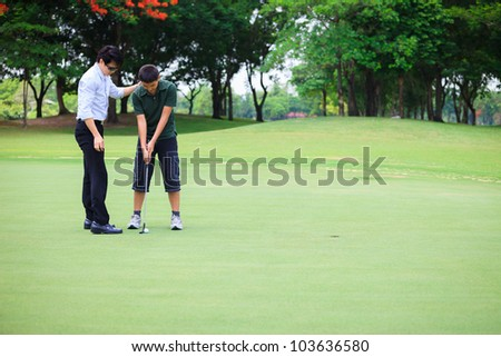 Professional teaching teenager boy to play golf