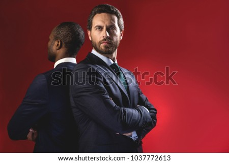 Professional team. Portrait of serious young bearded manager is standing with crossed arms while looking at camera confidently. He is posing back to back with his partner. Isolated and copy space